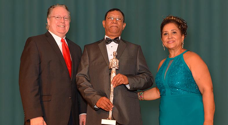Pedro Diaz Ballester, recibe su estatuilla de Premios Ilustres, de manos de la Dra. Maria Teresa Montilla, presidenta del Instituto de Estudios Latinos, y Michael J. Smith, presidente del Berkeley College.